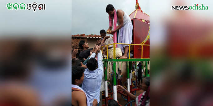 Devotees taking prasad from priests as the chariot rolls at Dharuadehi in Sundergarh on Rath Yatra